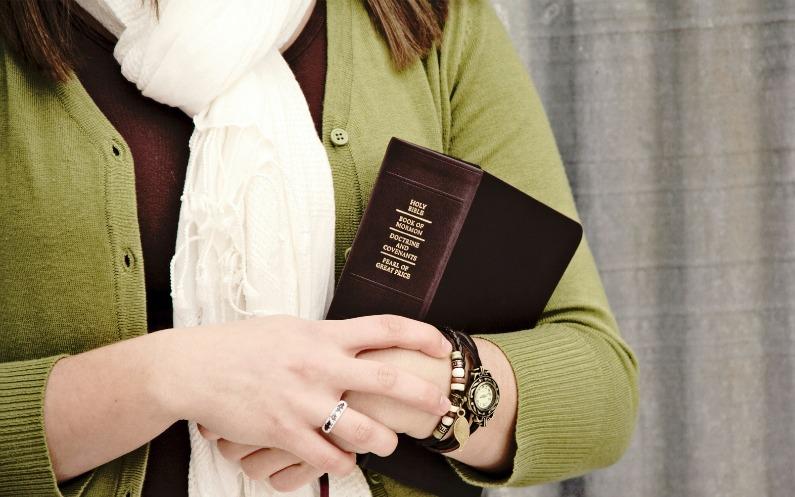 Мормонська жінка тримає в руках книгу Мормона