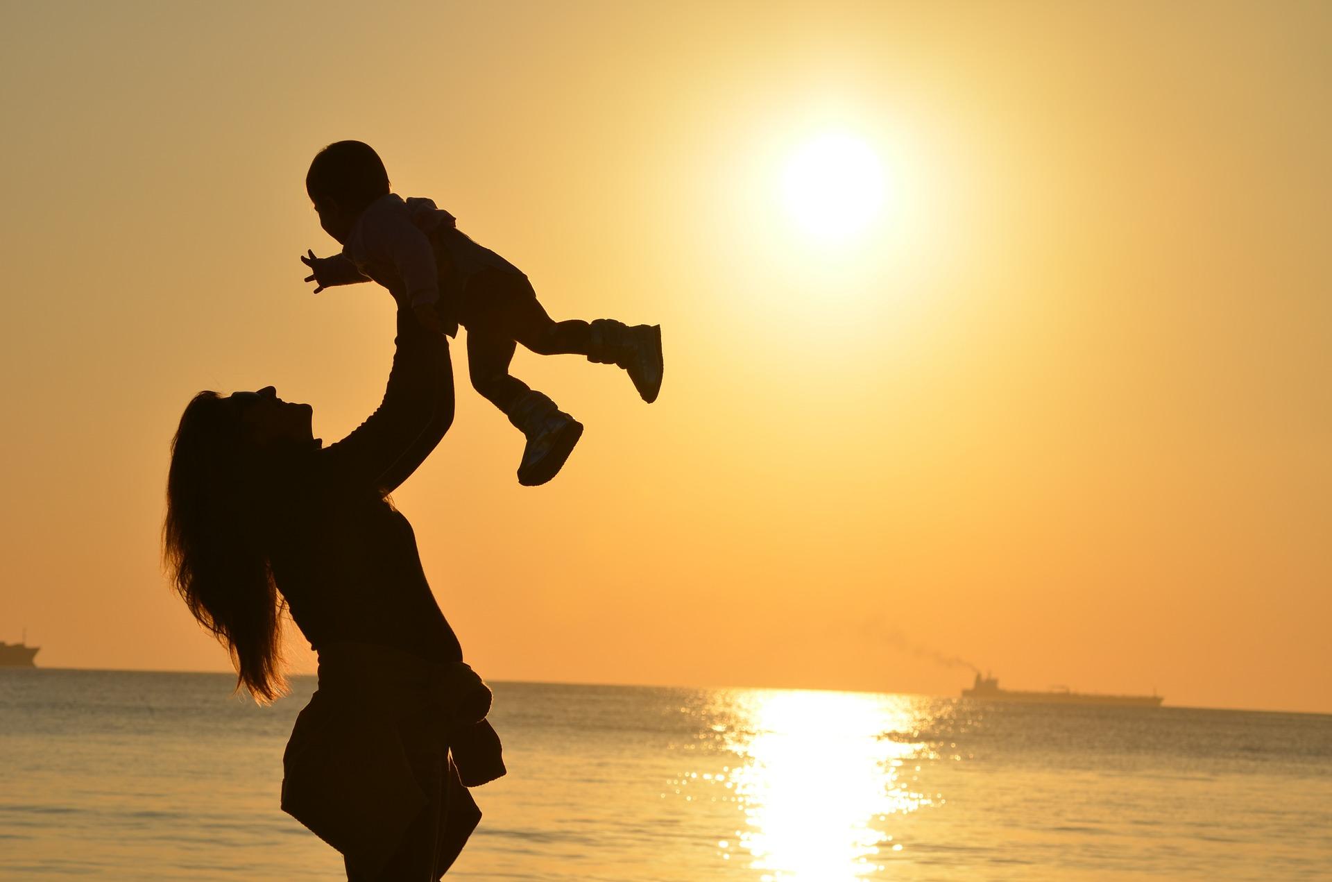 Жінка, яка відчуває щастя, бавлячись з дитиною