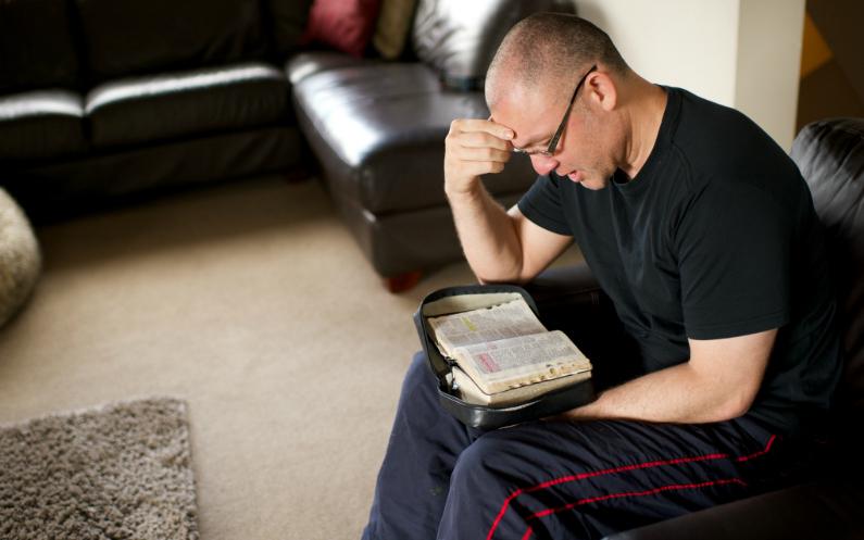 Чоловік наодинці вивчає Писання
