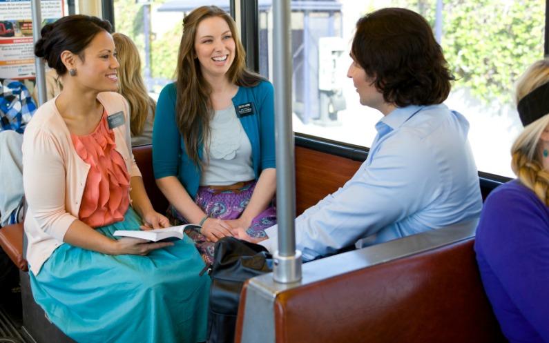 Жінка звертається до двох молодих дівчат, які є місіонерками Церкви