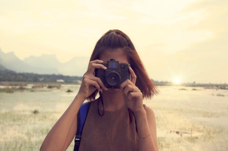 дівчина займається фотографуванням