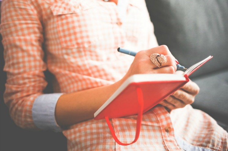 дівчина щаписує щось у щоденник
